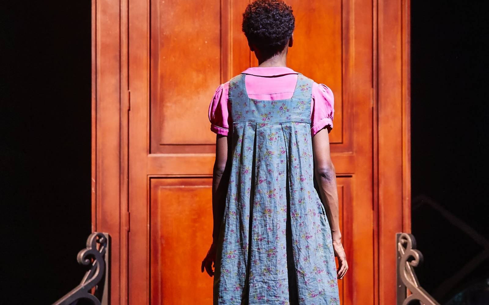 A woman seen from behind. She stands in front of a large wooden door