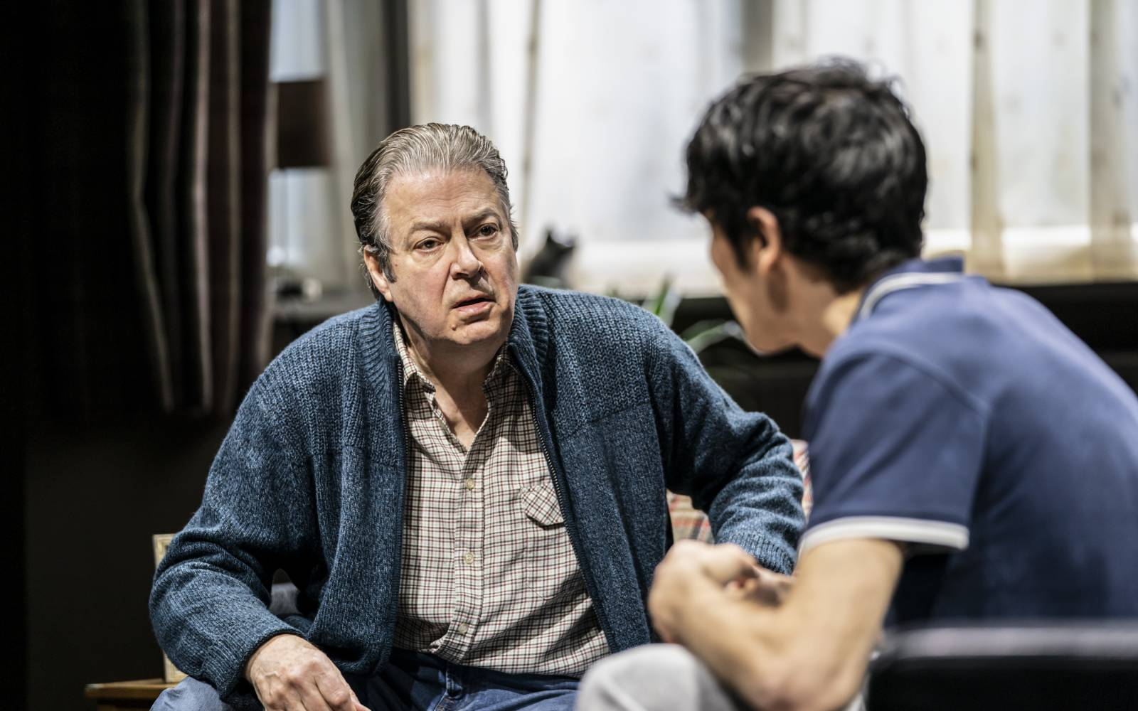 Roger Allam as Salter talks to Colin Morgan as his sons. Both are sitting, in modern dress