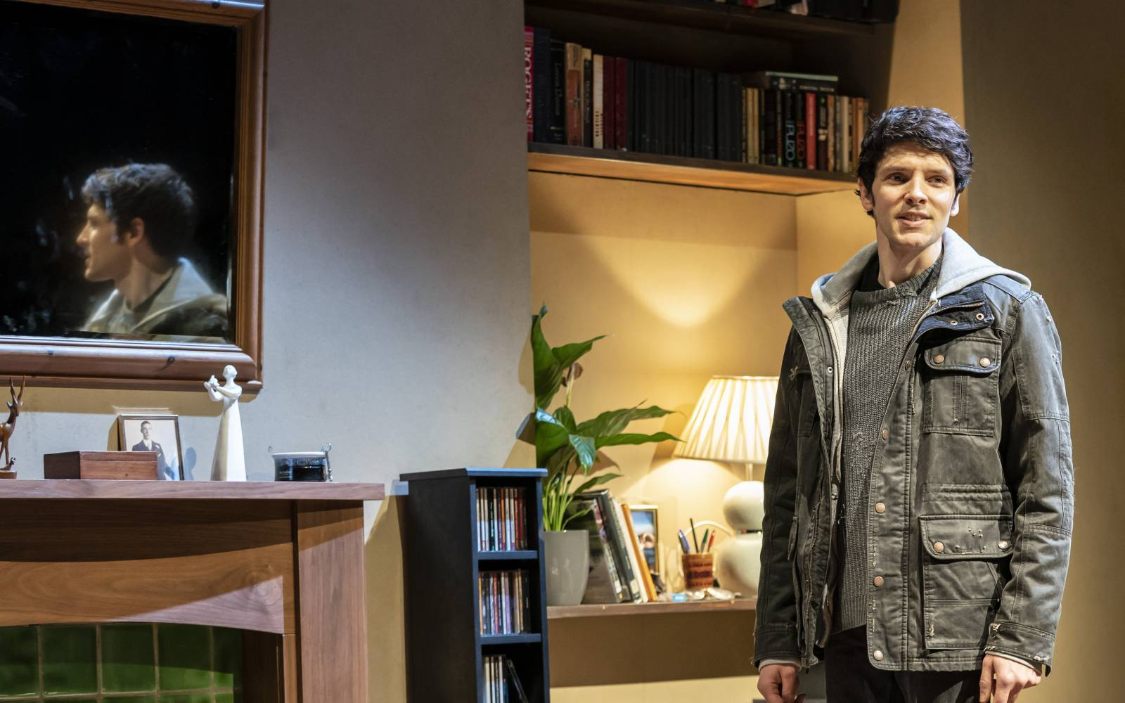 Colin Morgan as Bernard stands in a modern living room, in front of his reflection in the mirror