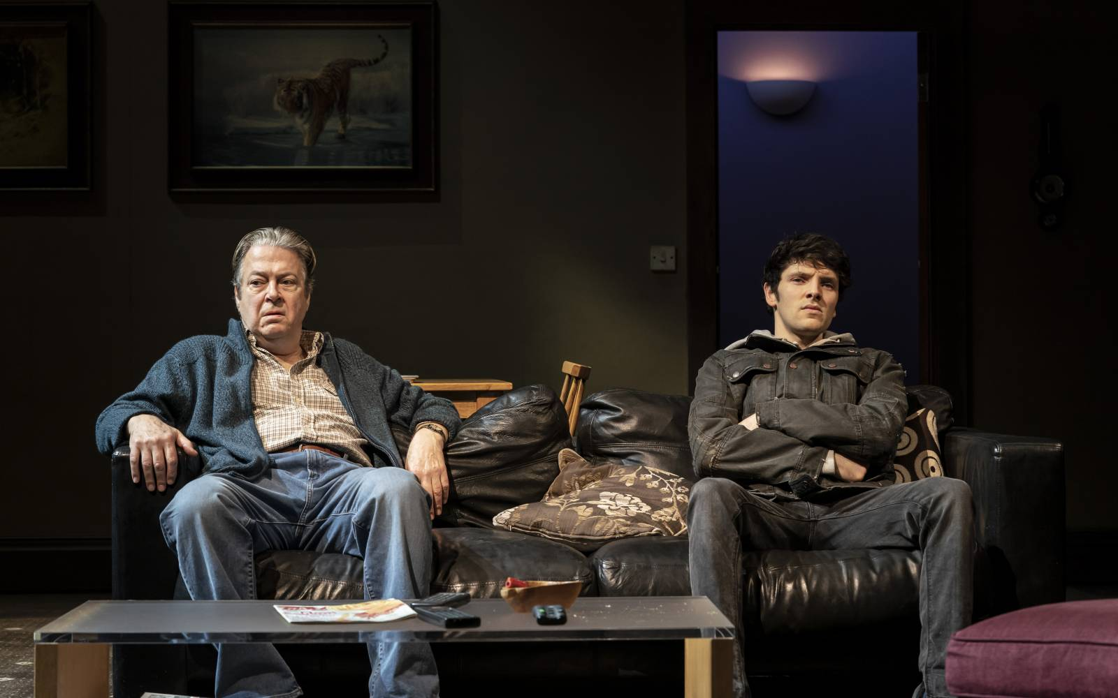 Roger Allam (father) and Colin Morgan (son) sit on a sofa, leaving space between them. They look unhappy