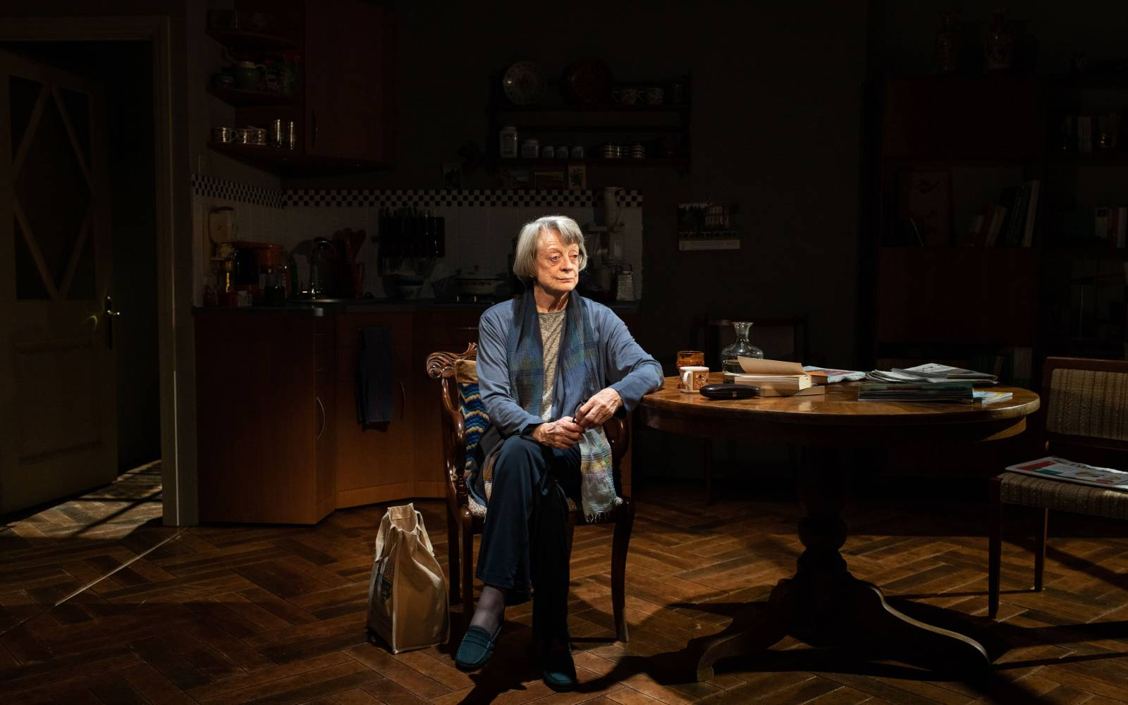 An older woman sits alone in a darkened kitchen, her elbow leaning against a table