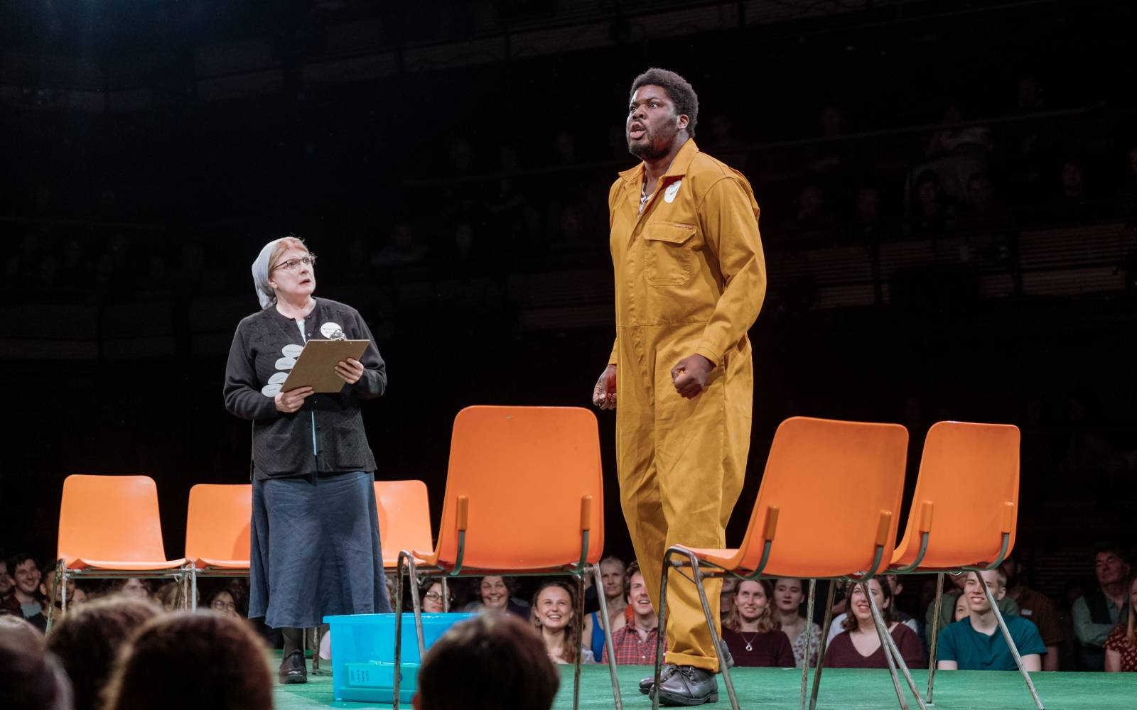 Hammed Animashaun (Bottom) performs, as Felicity Montagu (Quince) watches. They are surrounded by plastic chairs