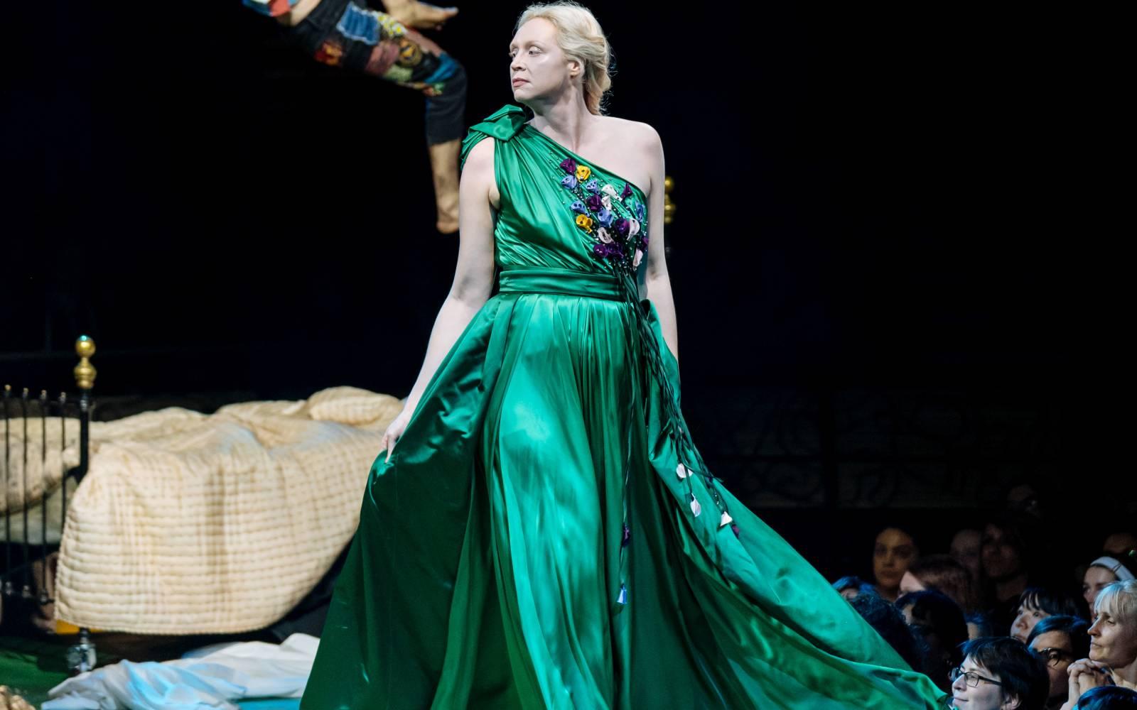 Gwendoline Christie (Hippolyta) strides forward, her emerald green dress billowing behind her