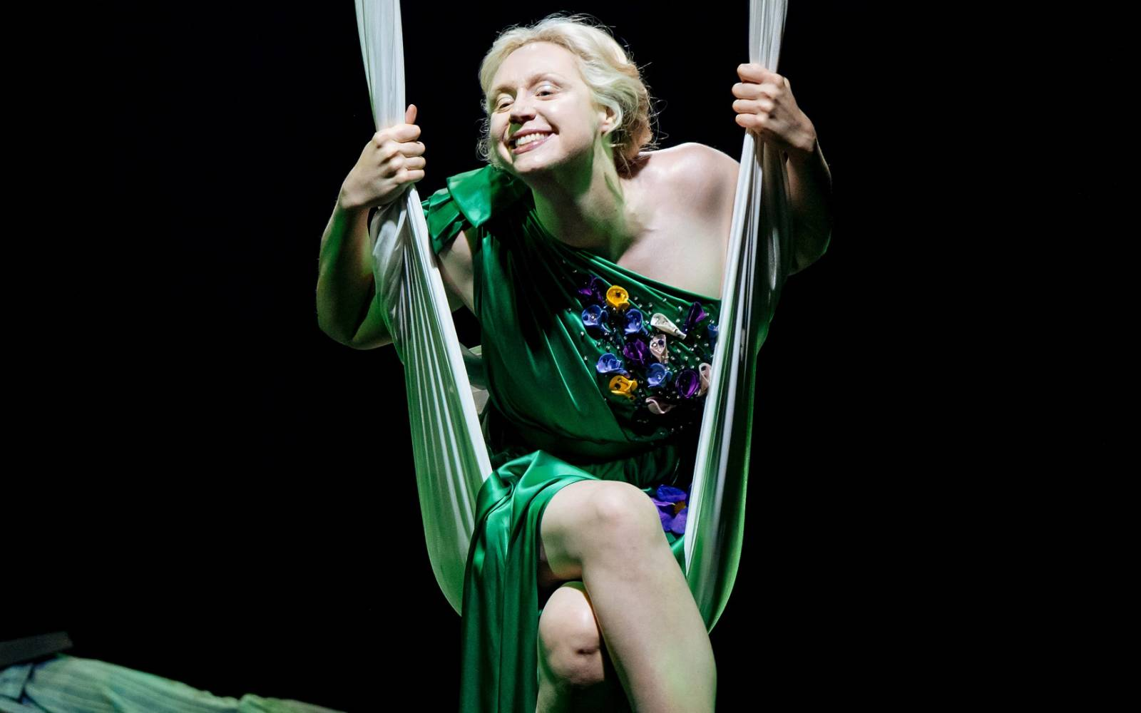 Gwendoline Christie (Titania) swings on a length of silk, with a cheeky grin