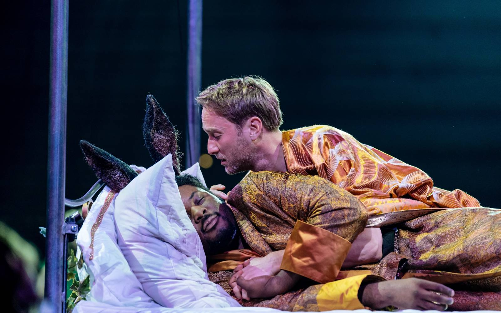 Hammed Animashaun (Bottom) sleeps in a bed, as Oliver Chris (Oberon) leans lustily over him