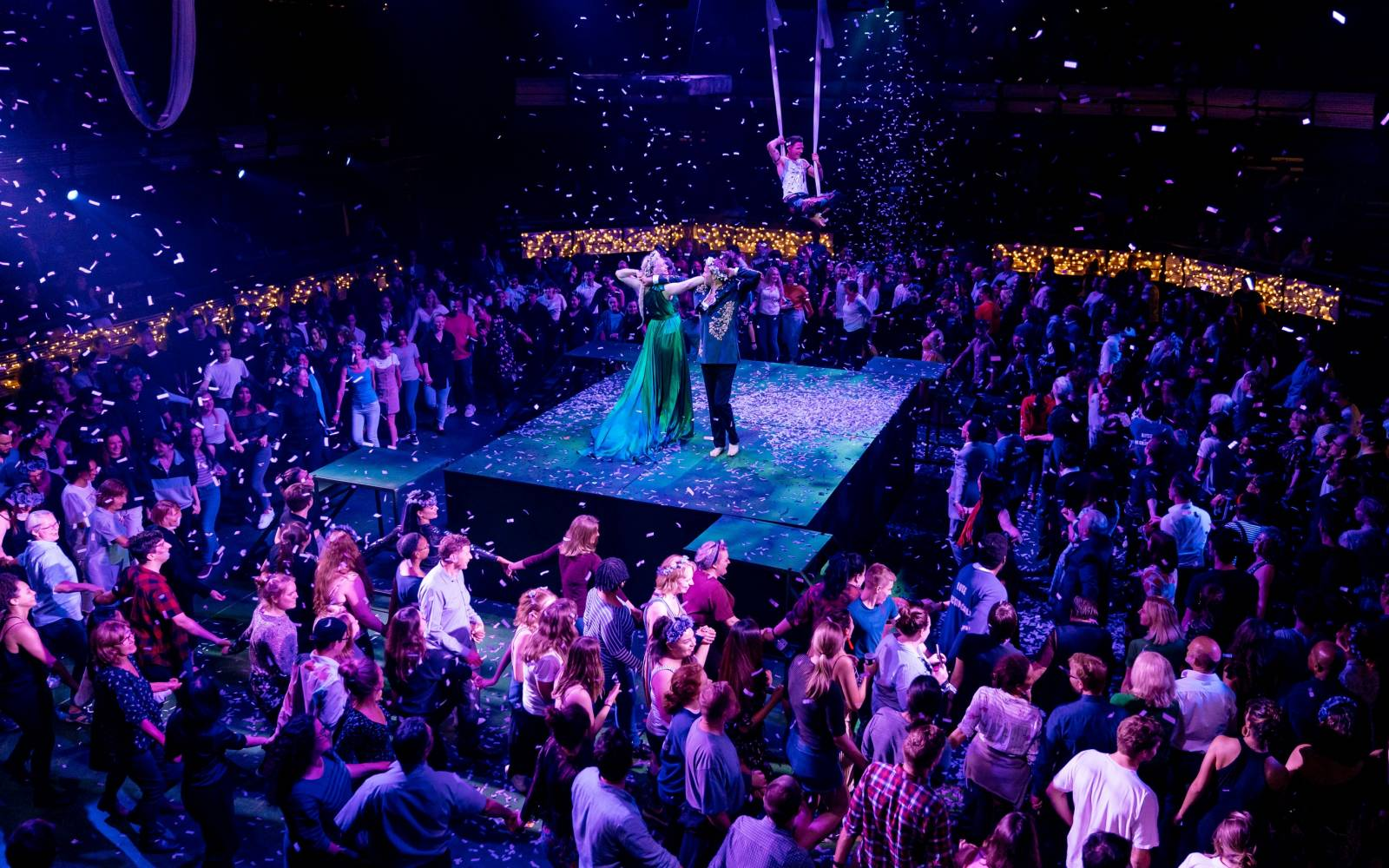 Gwendoline Christie (Titania) and Oliver Chris (Oberon) dance together under falling confetti, surrounded by a crowd