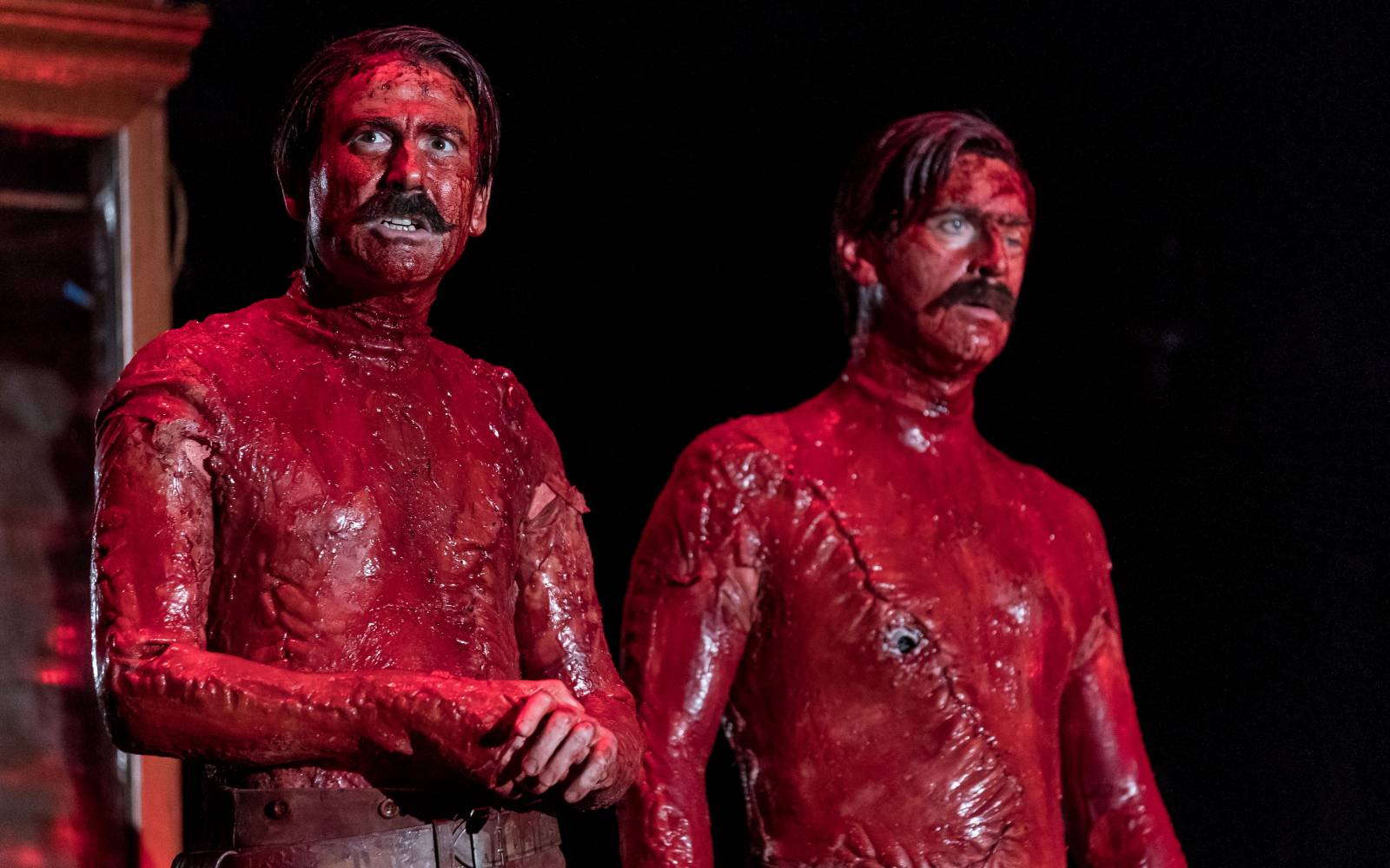 Two topless men, covered all over in blood. Their bodies are riddled with scars
