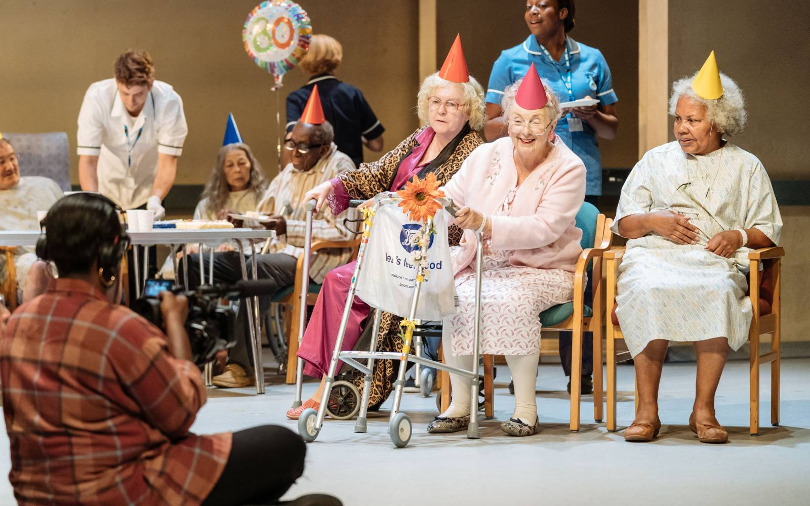 Elderly patients sit on chairs in a hospital. They are wearing paper party hats. Medical staff attend to them. In the foreground, with her back to the camera, a camerawoman films the scene