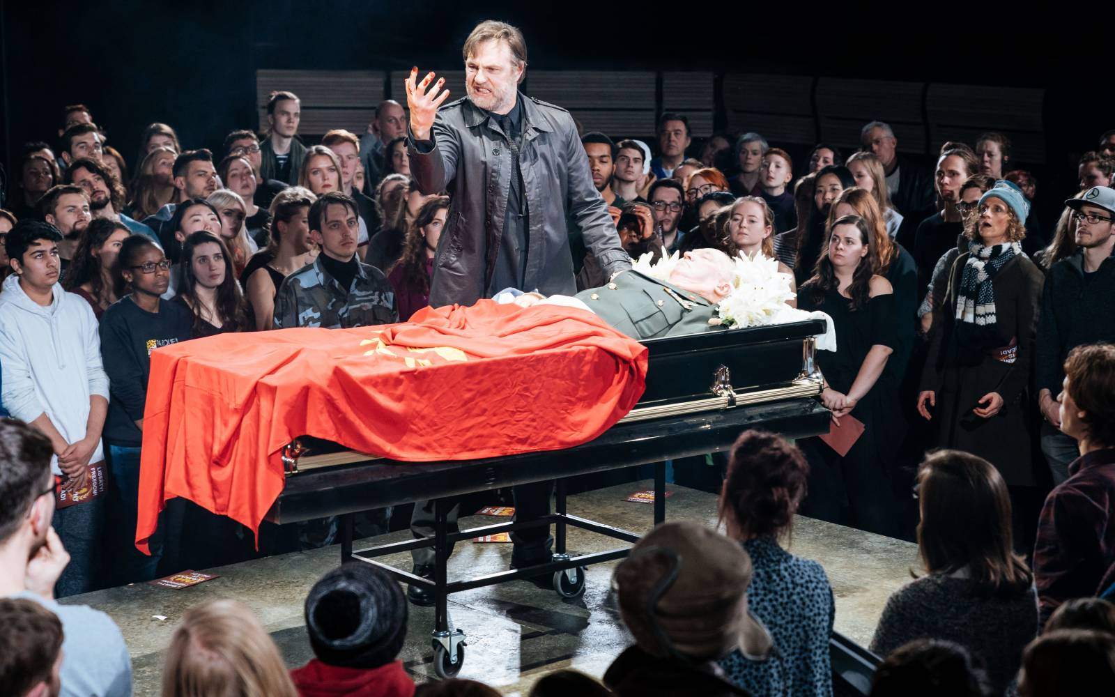 A man stares at his hand with fury. He stands over a body in a coffin, draped in a red flag, surrounded by a crowd