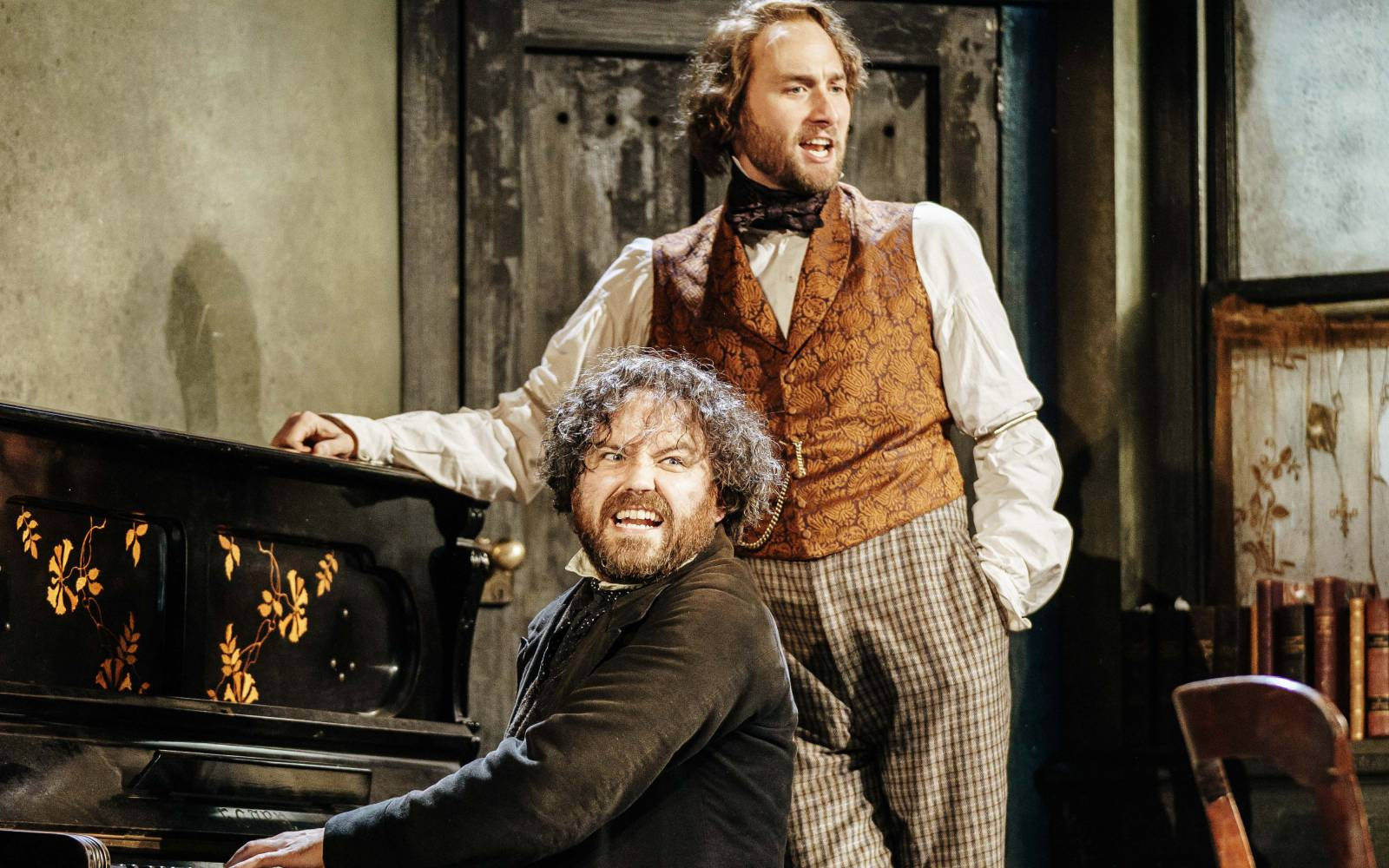 One man plays the piano, while another stands leaning against the piano, both in 19th-century dress