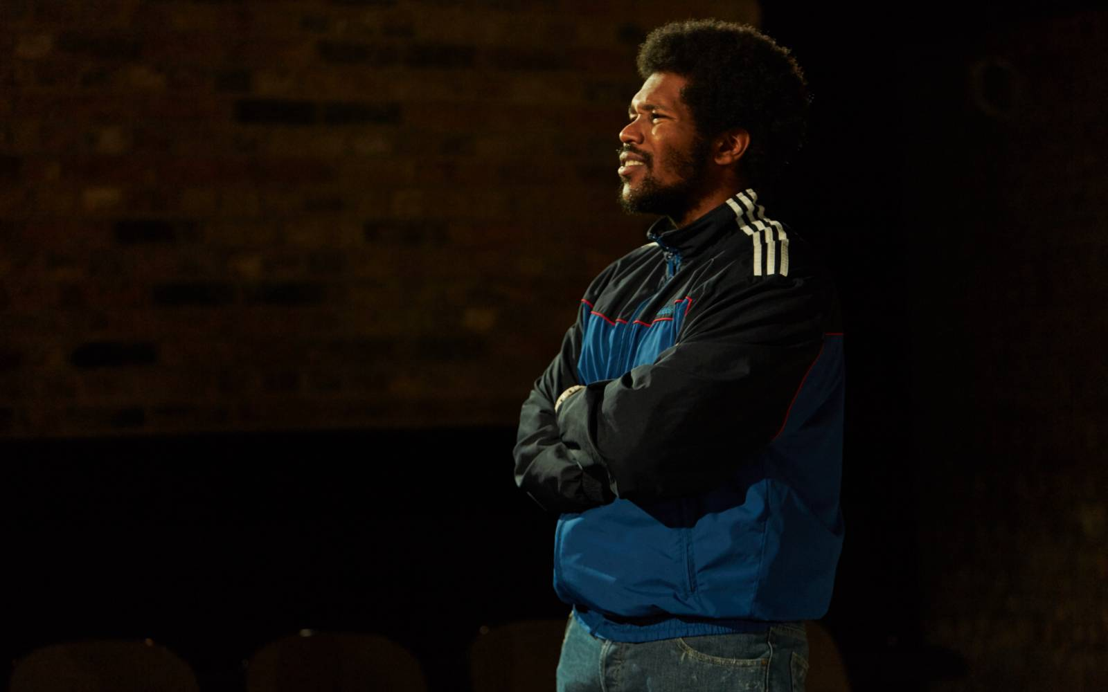 Side photo of Lladel Bryant. He's looking out to the audience and squinting, his arms crossed. He has short afro hair and a beard. He's wearing dark jeans and a light and dark blue sports jacket with 3 white stripes down the arm.