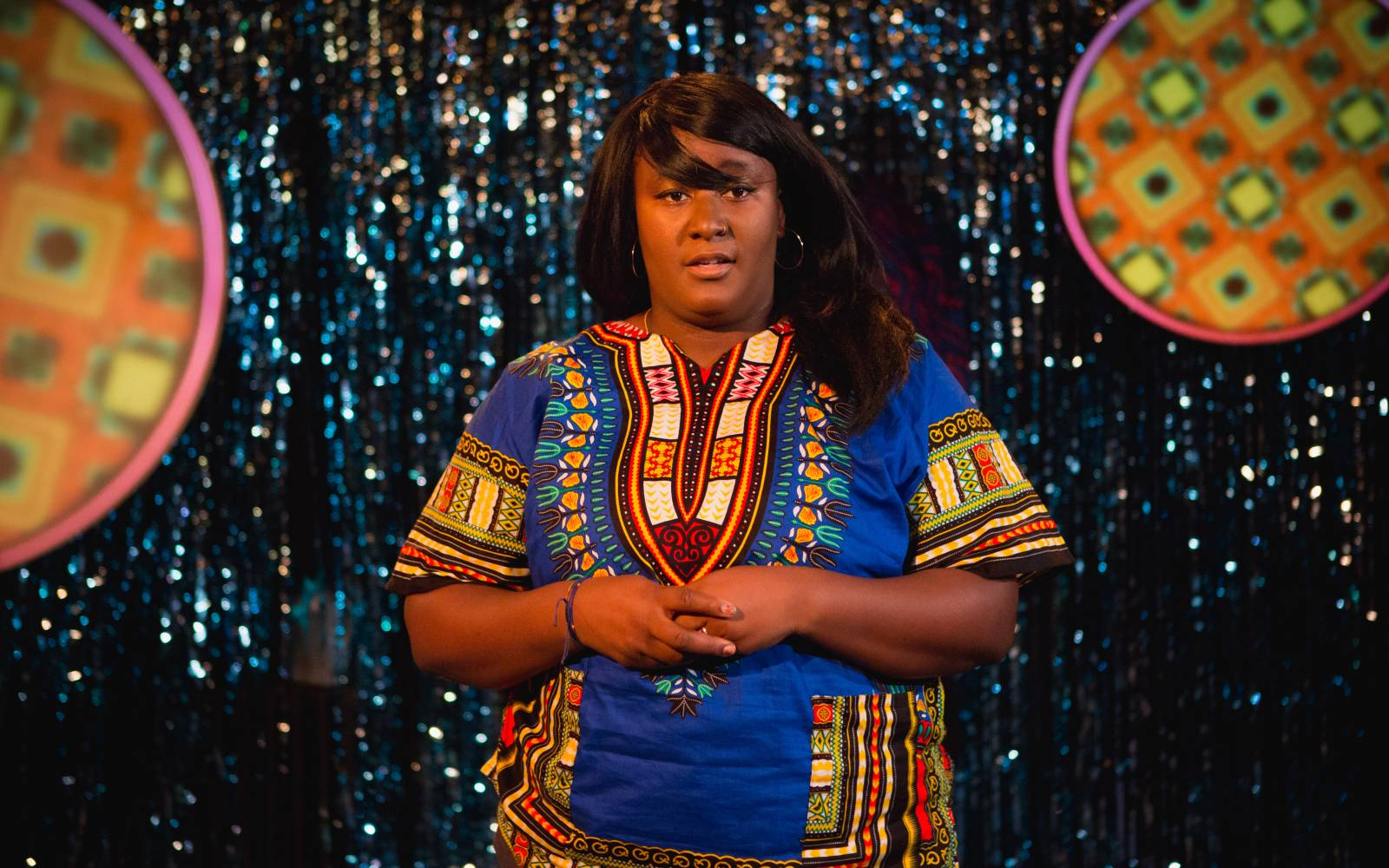 A sparkly blue tassled backdrop. A woman (Yolanda Mercy) is stood in the centre, wearing a dashiki top with bold blue, reds and yellows. Her hands are entwined in front of her and she's looking out into the audience. She's wearing large hoops in her ears and her hair is long, straight with a side fringe sweeping over her face.