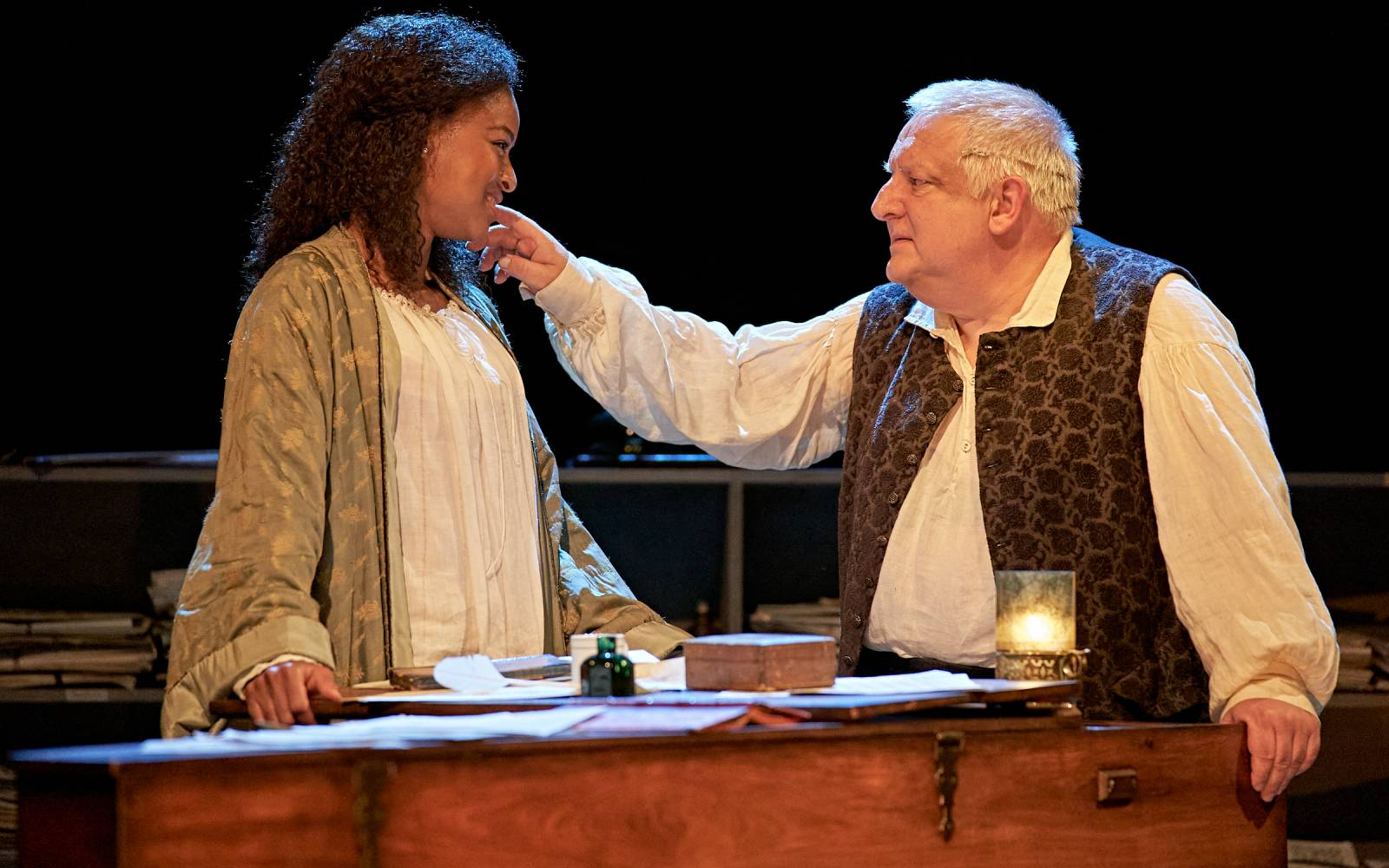 Racheal Ofori and Simon Russell Beale are stood behind the harpsicord. They're looking at each other and his hand is touching her cheek.